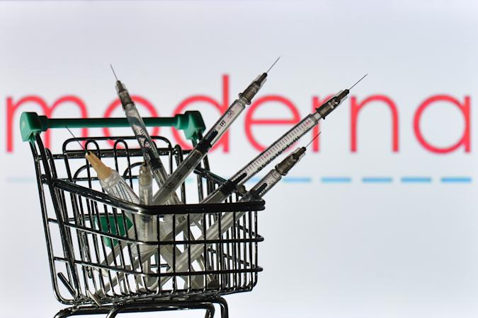 Medical syringes in the mini shopping trolley are seen in front of the Moderna logo displayed on a screen. On Friday, 28 May 2021, in Dublin, Ireland. (Photo by Artur Widak/NurPhoto via Getty Images)