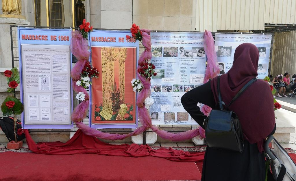 A woman looks at signs as she takes part in a rally marking the 25th anniversary of the 1988 massacre of Iranian political prisoners