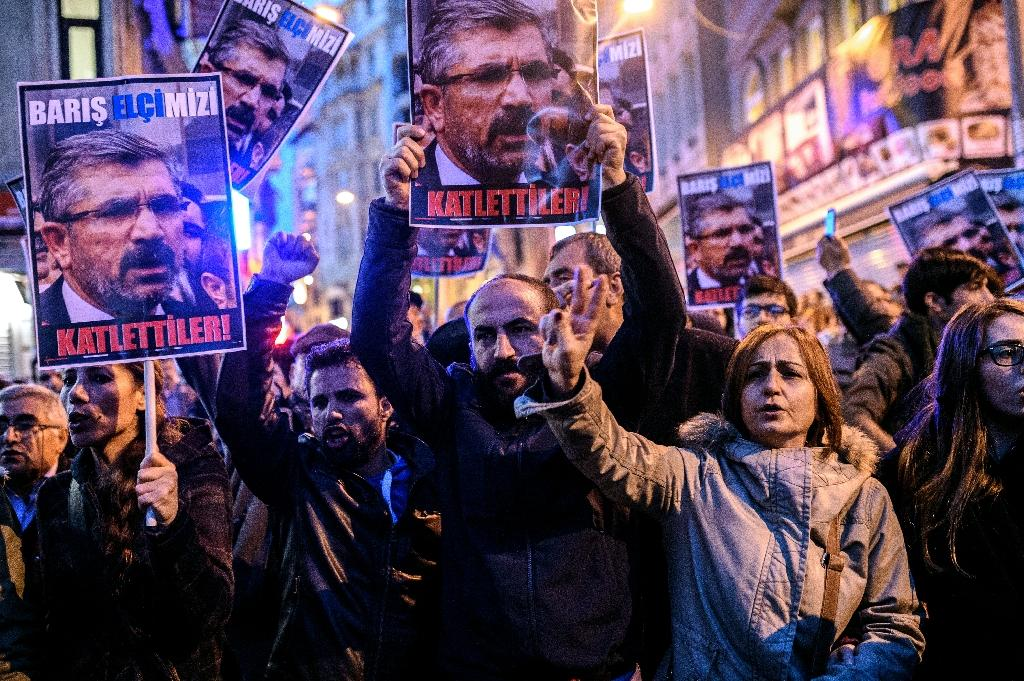 "Protesters hold pictures of Kurdish lawyer Tahir Elci reading ""They slaughtered him!"" during a demonstration in Istanbul after he was killed in Diyarbarkir on November 28, 2015 (AFP Photo/Ozan Kose)"
