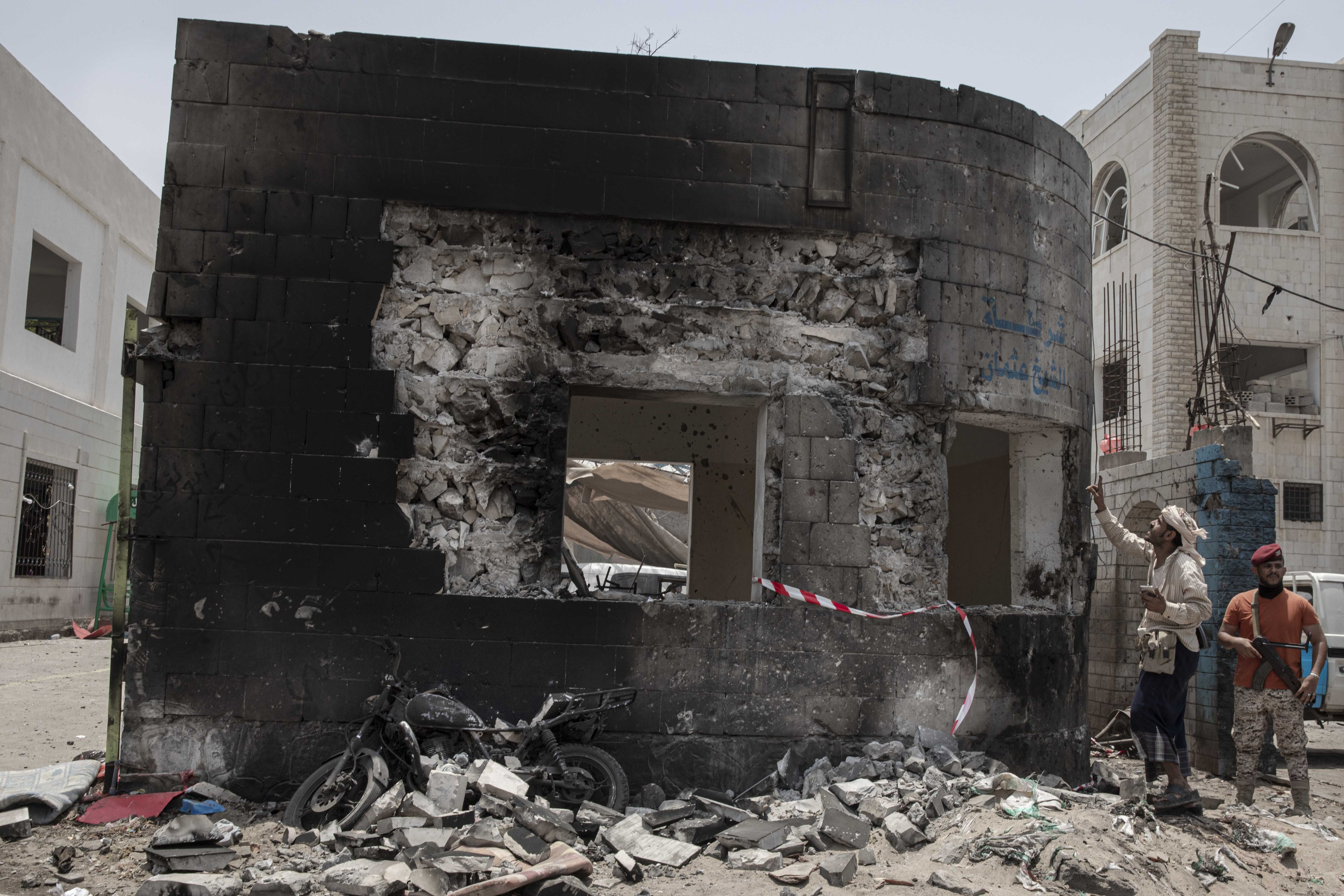 Security forces inspect the site of a deadly attack in Aden, Yemen, Thursday, Aug. 1, 2019. Yemen's rebels fired a ballistic missile at a military parade Thursday in the southern port city of Aden as coordinated suicide bombings targeted a police station in another part of the city. The attacks killed over 50 people and wounded dozens. (AP Photo/Nariman El-Mofty)