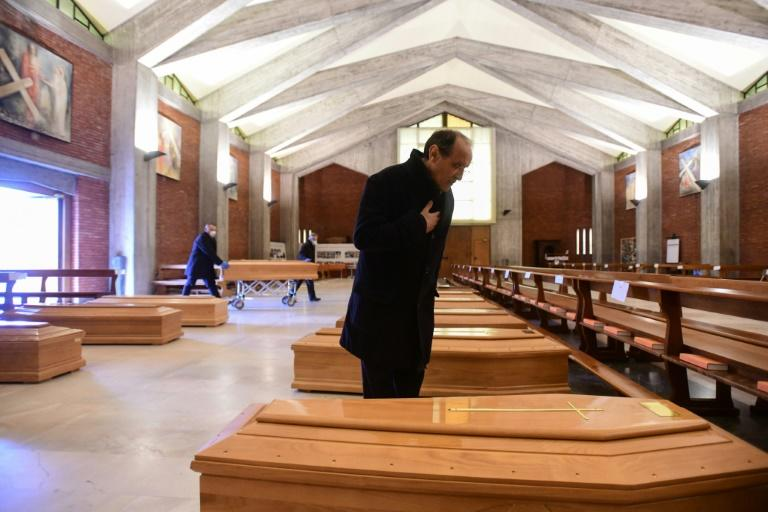 A priest says a quiet prayer over the rows of coffins at the warehouse on Bergamo's outskirts (AFP Photo/Piero CRUCIATTI)