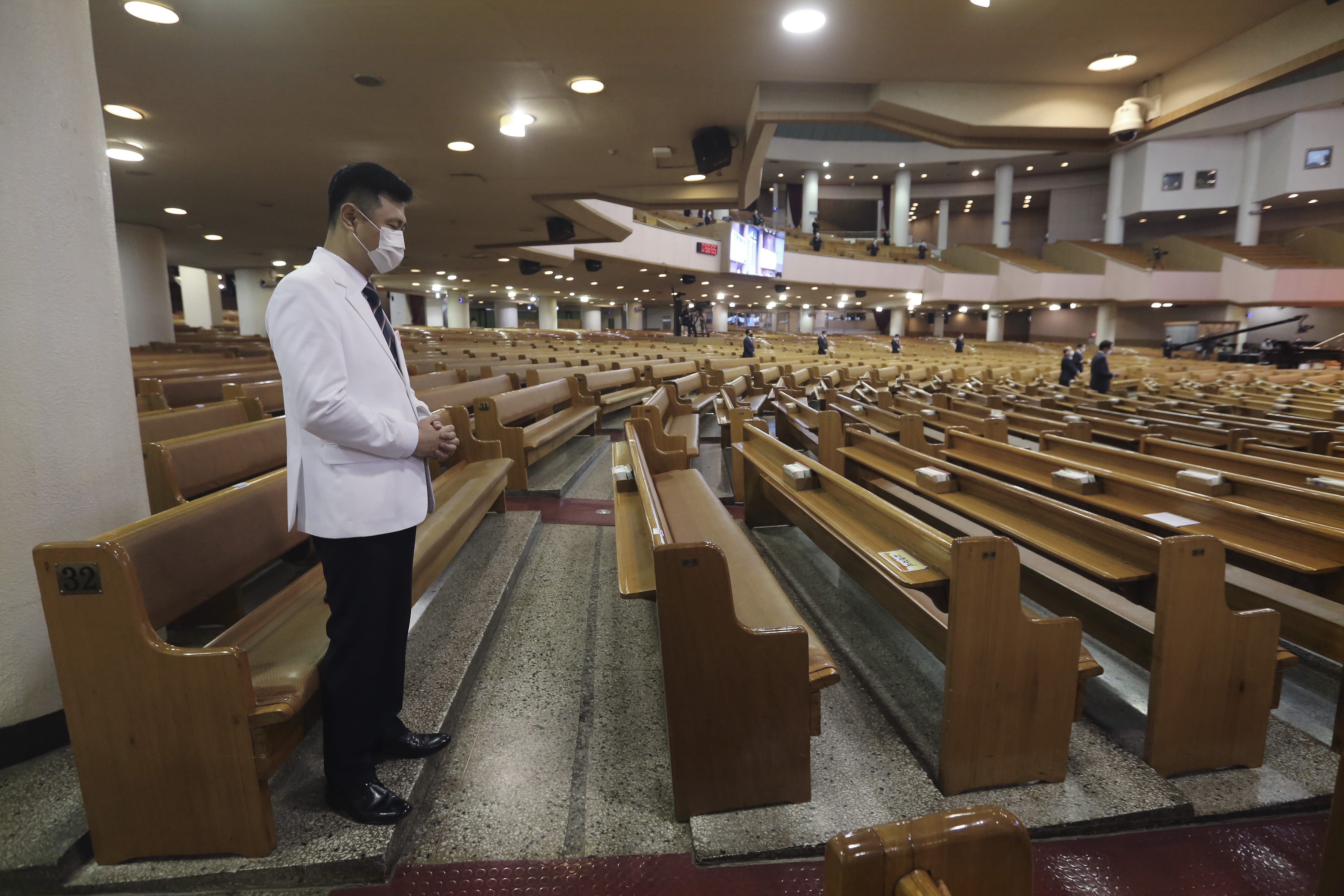 A pastor wearing a face mask to help protect against the spread of the coronavirus prays during a service at the Yoido Full Gospel Church in Seoul, South Korea, Sunday, Sept. 20, 2020. South Korea's new coronavirus tally has fallen below 100 for the first time in more than a month. (AP Photo/Ahn Young-joon)