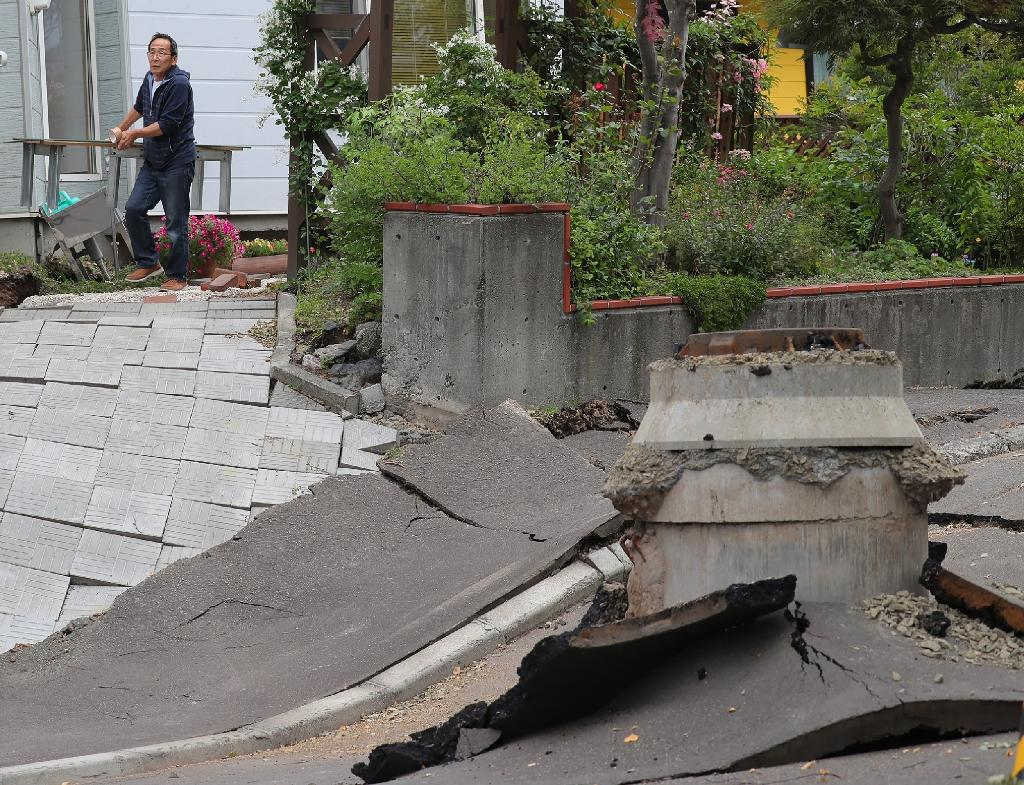 A resident cleans his house next to a damaged street in Sapporo, the regional capital (AFP Photo/JIJI PRESS)