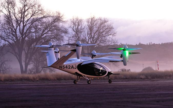 The Joby Aviation electric air taxi sits on a runway during pinkish pre-dawn hours with mist hanging among the trees in the background.