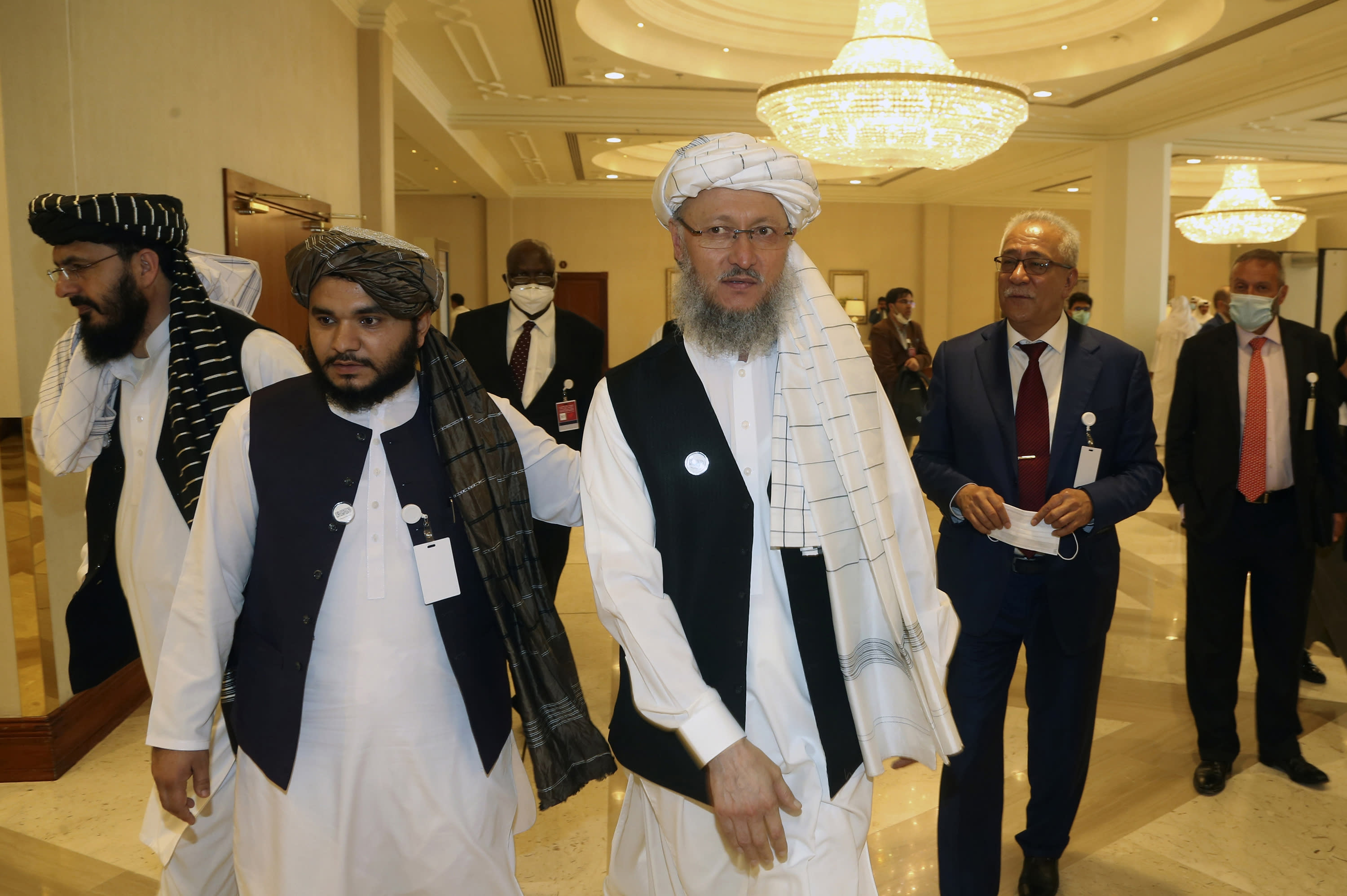 Deputy Head of Political Office of the Taliban Abdul Salam Hanafi, center, heads to attend the opening session of the peace talks between the Afghan government and the Taliban in Doha, Qatar, Saturday, Sept. 12, 2020. (AP Photo/Hussein Sayed)