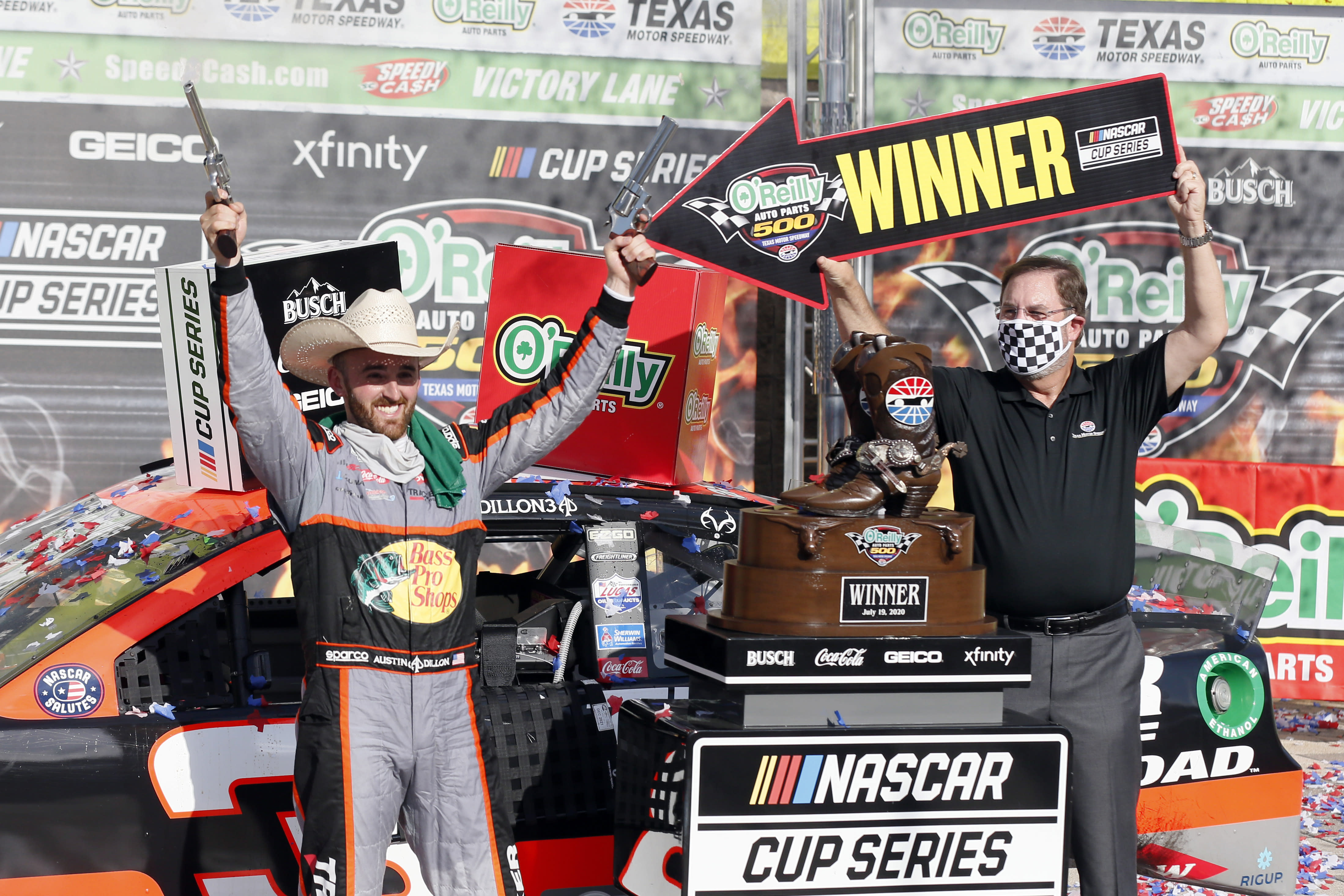 """Texas Motor Speedway President and General Manager Eddie Gossage, right, holds a """"winner"""" sign as Austin Dillon, left, celebrates by firing six shooters after winning the NASCAR Cup Series auto race at Texas Motor Speedway in Fort Worth, Texas, Sunday, July 19, 2020. (AP Photo/Ray Carlin)"""
