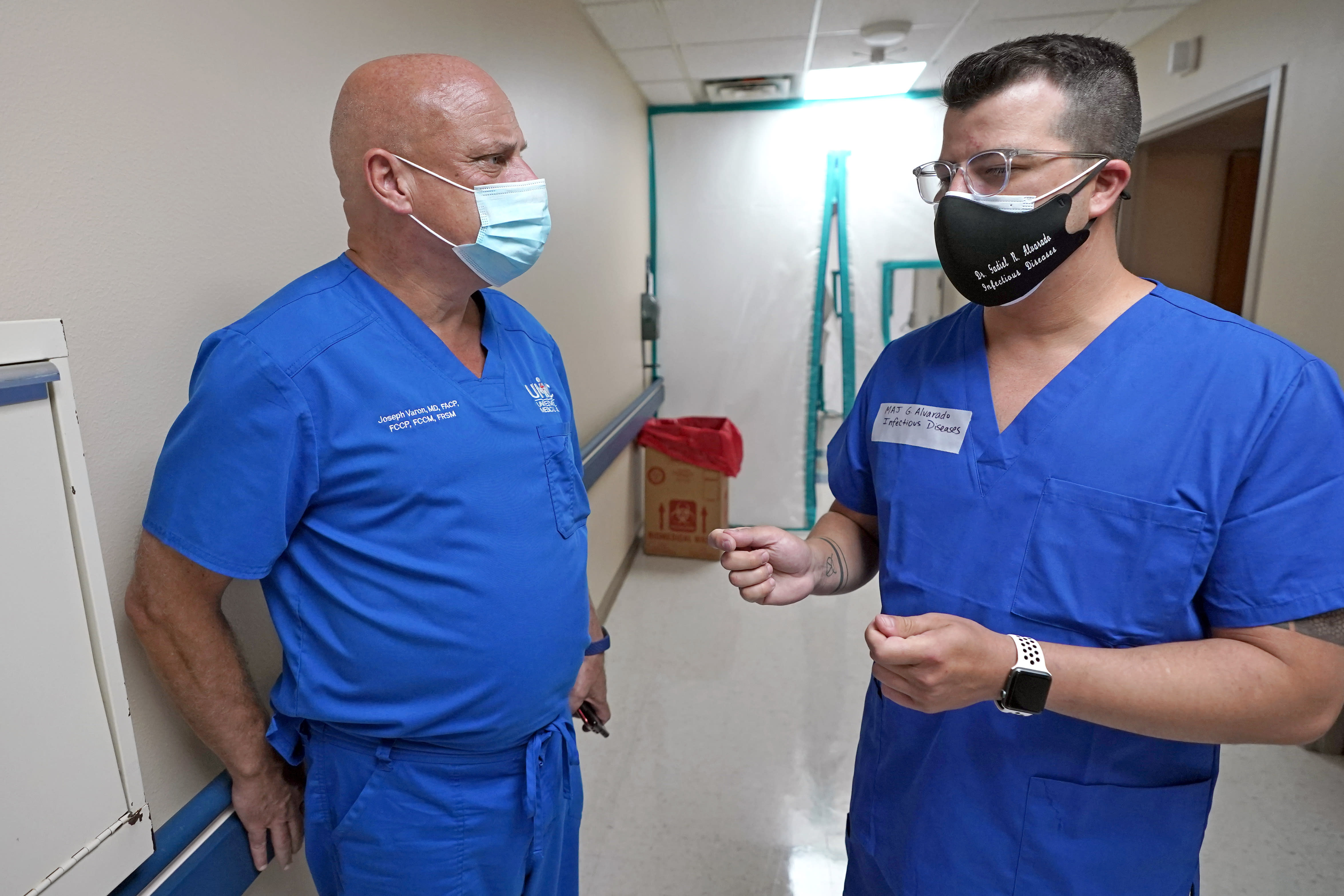 FILE - In this July 16, 2020 file photo, Infectious Disease Physician Army Maj. Gadiel Alvarado, right, with the Urban Augmentation Medical Task Force, talks with United Memorial Medical Center's Dr. Joseph Varon, inside a newly setup hospital wing in Houston. Texas reported a new daily record for virus deaths Friday and more than 10,000 confirmed cases for the fourth consecutive day. (AP Photo/David J. Phillip)