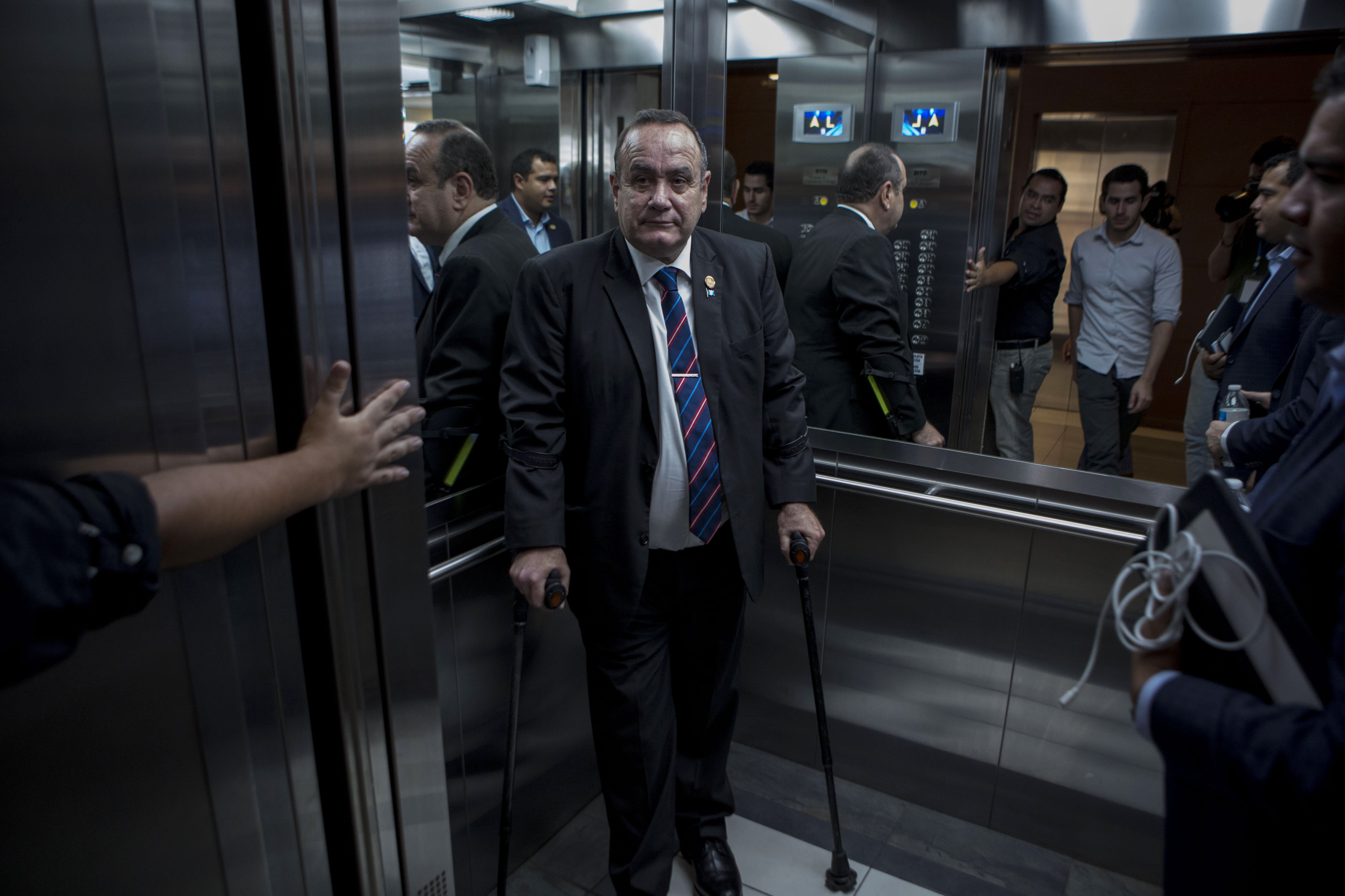 """Guatemala's President-elect Alejandro Giammattei stands in an elevator as he arrives for an interview in Guatemala City, Tuesday, Aug. 13, 2019. Giammattei said Tuesday that Guatemala will not be able to hold up its side of an immigration agreement with the United States by serving as a """"safe third country"""" for asylum seekers. (AP Photo/Oliver de Ros)"""