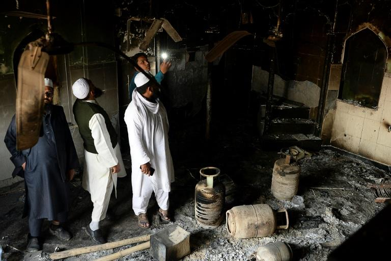 Muslim men check the interior of a partially burnt mosque on March 1, 2020 after communal riots in New Delhi (AFP Photo/Sajjad HUSSAIN )
