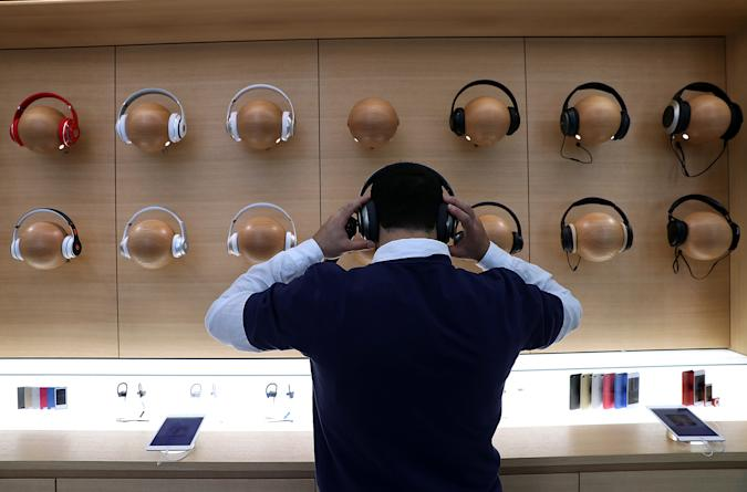 """SAN FRANCISCO, CA - MAY 19:  An Apple Store employee tries on a pair of headphones during a press preview of the new flagship Apple Store on May 19, 2016 in San Francisco, California. Apple is preparing to open its newest flagship store in San Francisco's Union Square on Saturday May 21. The new store features new design elements as well as community programs including the """"genius grove"""" where where customers can get support under a canopy of local trees and """"the plaza"""" a public space that will be open 24 hour a day. Visitors will enter the store through 42-foot tall sliding glass doors.  (Photo by Justin Sullivan/Getty Images)"""