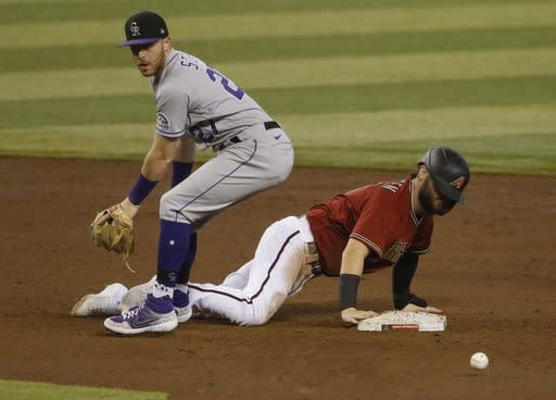 Colorado Rockies shortstop Trevor Story, left, looks for the ball after Arizona Diamondbacks' Wyatt Mathisen dove back into second base during the fourth inning of a baseball game Sunday, Sept. 27, 2020, in Phoenix. (AP Photo/Darryl Webb)