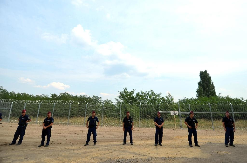 Hungarian soldiers stand in front of the first completed elements of the 150 meter-long fence on the border with Serbia (AFP Photo/Csaba Segsvari)