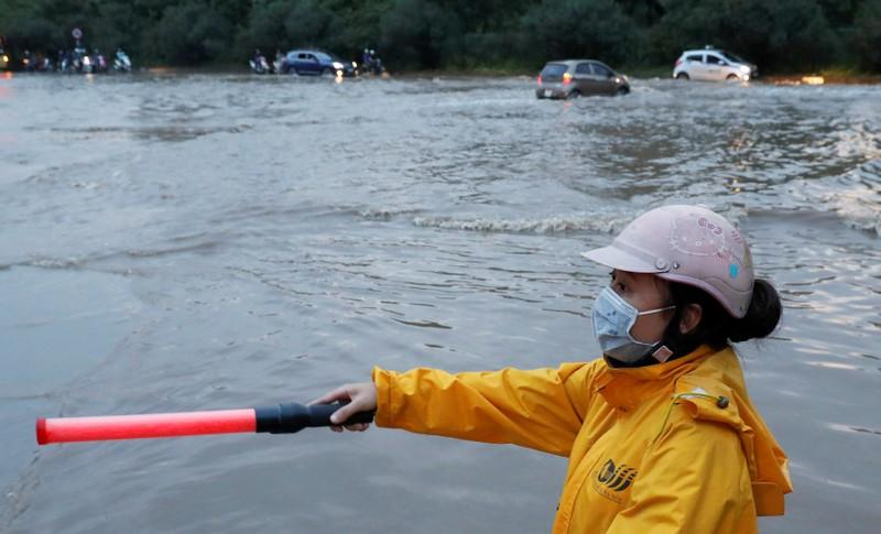 A woman directs traffic on a flooded road after typhoon Wipha in Hanoi