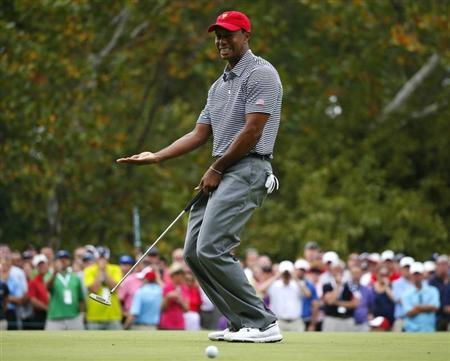 U.S. team member Tiger Woods reacts as he misses a putt on the first hole during the Foursome matches for the 2013 Presidents Cup golf tournament at Muirfield Village Golf Club in Dublin, Ohio