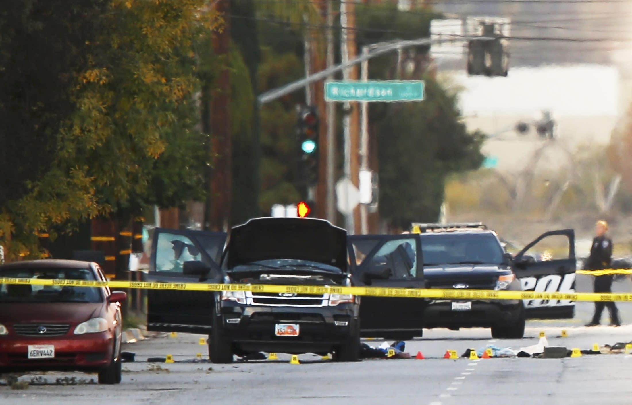 A police investigator is seen around a vehicle (C) in which two suspects were shot following a mass shooting in San Bernardino, California December 3, 2015. Authorities on Thursday were working to determine why Syed Rizwan Farook, 28, and Tashfeen Malik, 27, who had a 6-month-old daughter together, opened fire at a holiday party of his co-workers in Southern California, killing 14 people and wounding 17 in an attack that appeared to have been planned. REUTERS/Mike Blake
