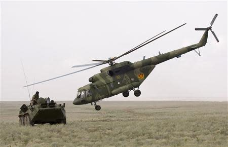 An MI-17 helicopter flies by an armoured personnel carrier (APC) during the Steppe Eagle 2010 joint tactical military exercise at Ili military range, outside Almaty in this August 24, 2010 file photo. REUTERS/Shamil Zhumatov/Files