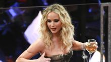 Photos of Jennifer Lawrence climbing over seats while clutching wine are making the internet very happy
