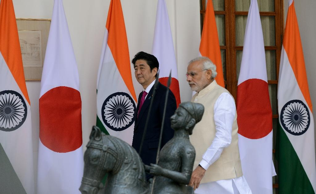 India's Prime Minister Narendra Modi walks with Japan's Prime Minister Shinzo Abe at Hyderabad House in New Delhi on December 12, 2015
