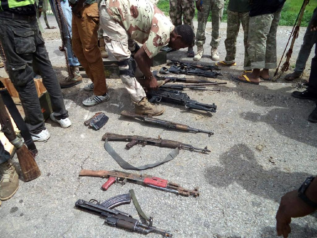 A soldier inspecting seized weapons from Islamist Boko Haram fighters in July