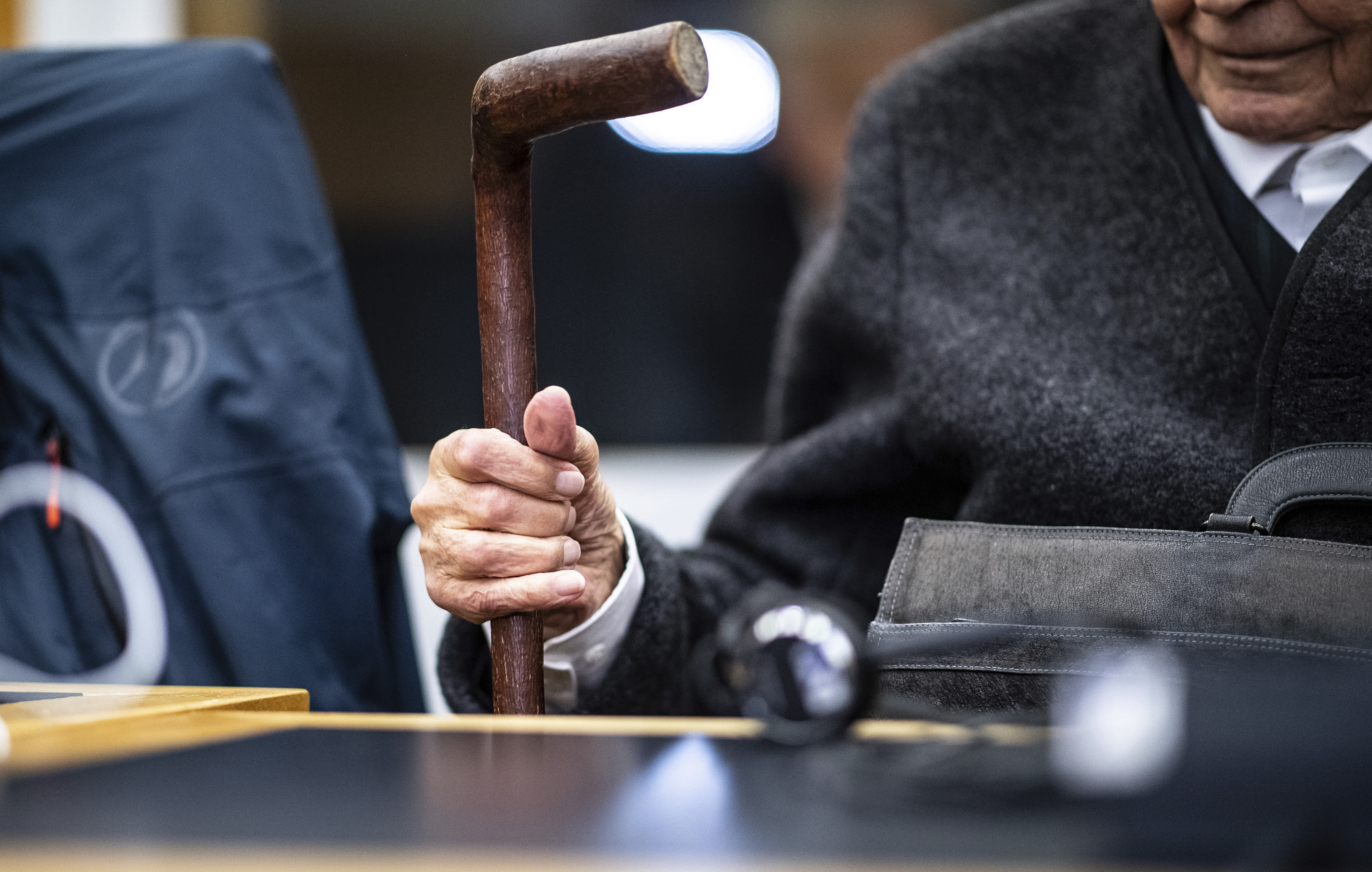 Johann Rehbogen, a 94-year-old former SS enlisted man, who is accused of hundreds of counts of accessory to murder for alleged crimes committed during the years he served as a guard at the Nazis' Stutthof concentration camp, waits for the beginning of the third day of his trial at the regional court in Muenster, western Germany, Tuesday, Nov. 13, 2018. (Guido Kirchner/pool photo via AP)
