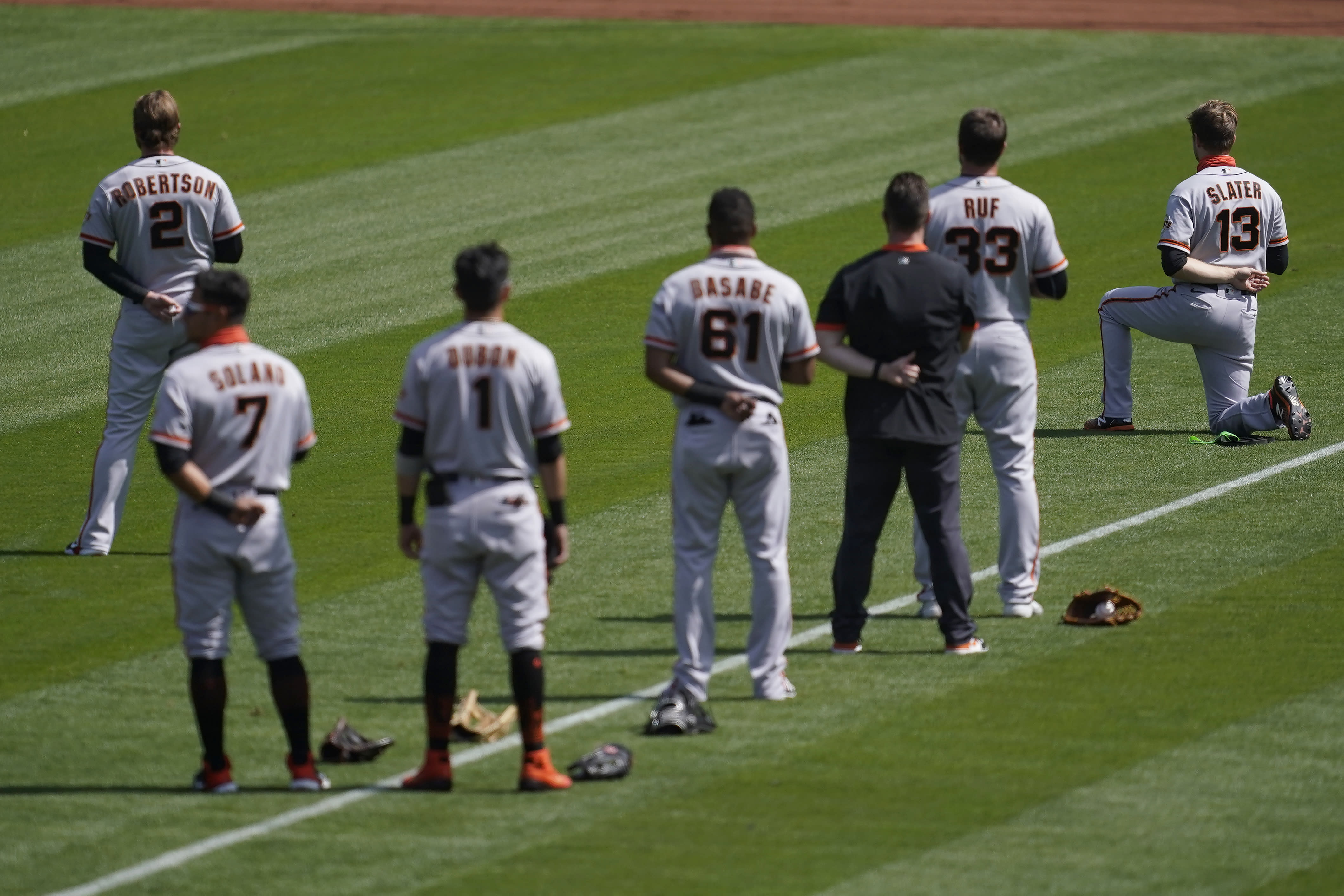 San Francisco Giants' Austin Slater (13) kneels during the national anthem before a baseball game against the Oakland Athletics in Oakland, Calif., Saturday, Sept. 19, 2020. (AP Photo/Jeff Chiu)