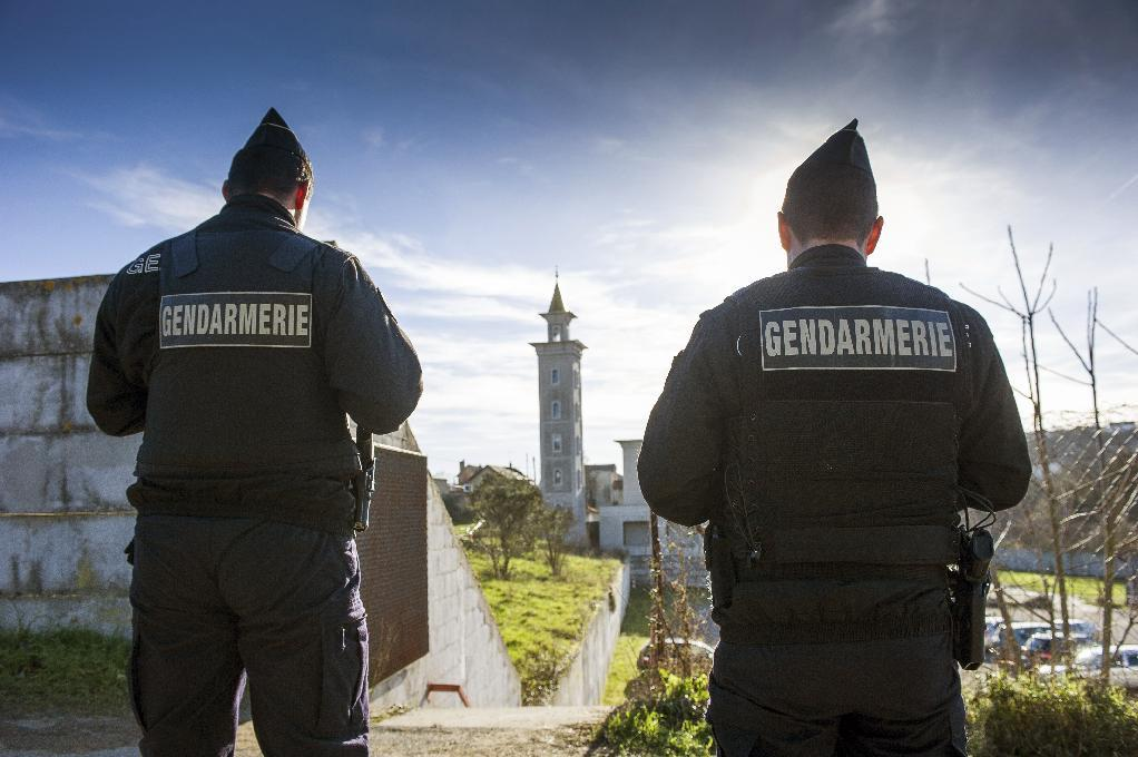French police officers are posted outside the mosque of Poitiers, west-central France, following what is believed to be an arson attack, on January 12, 2015