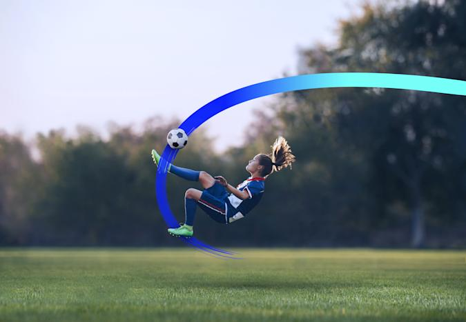 Dedicated female soccer player doing the bicycle kick on a soccer match at a stadium.