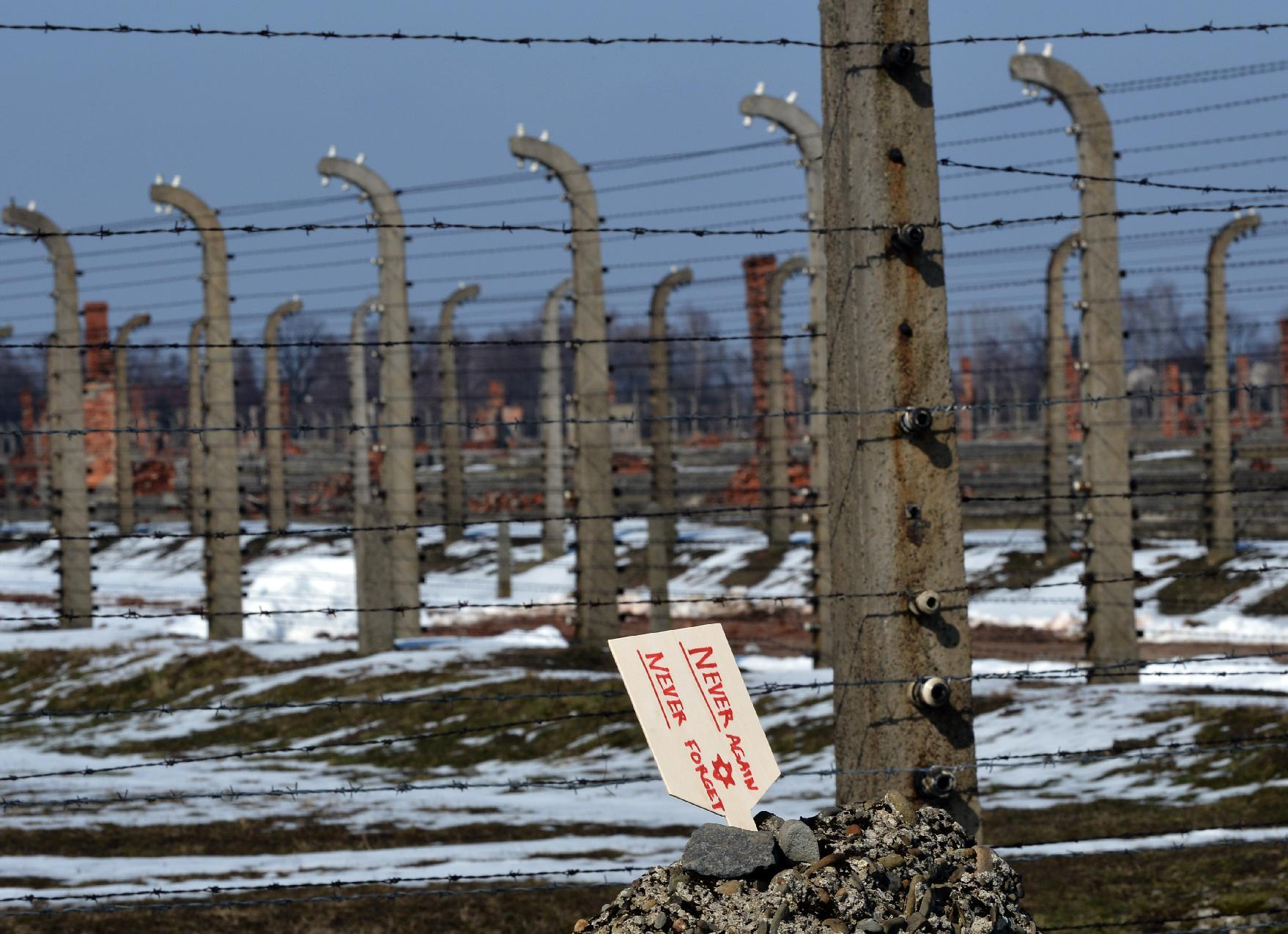 Photo taken on April 8, 2013 shows a memorial plaque stuck into a pile of pebbles on the fence of Auschwitz-Birkenau concentration camp, in Oswiecim, Poland (AFP Photo/Janek Skarzynski)