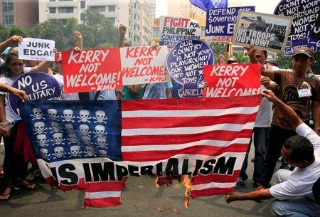 Protesters burn a replica of an American flag while denouncing the visit of U.S. Secretary of State John Kerry and the Supreme Court's decision to uphold, with finality, the constitutionality of the Enhanced Defense Cooperation Agreement (EDCA) during a protest outside the U.S. embassy in metro Manila, Philippines July 27, 2016. REUTERS/Romeo Ranoco
