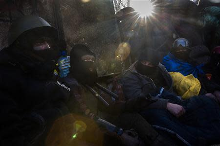 Anti-government protesters huddle under blankets as temperatures stand at minus 20 degrees Celsius (minus 4 degrees Fahrenheit) at a barricade near Independence Square in Kiev, January 30, 2014. REUTERS/Thomas Peter