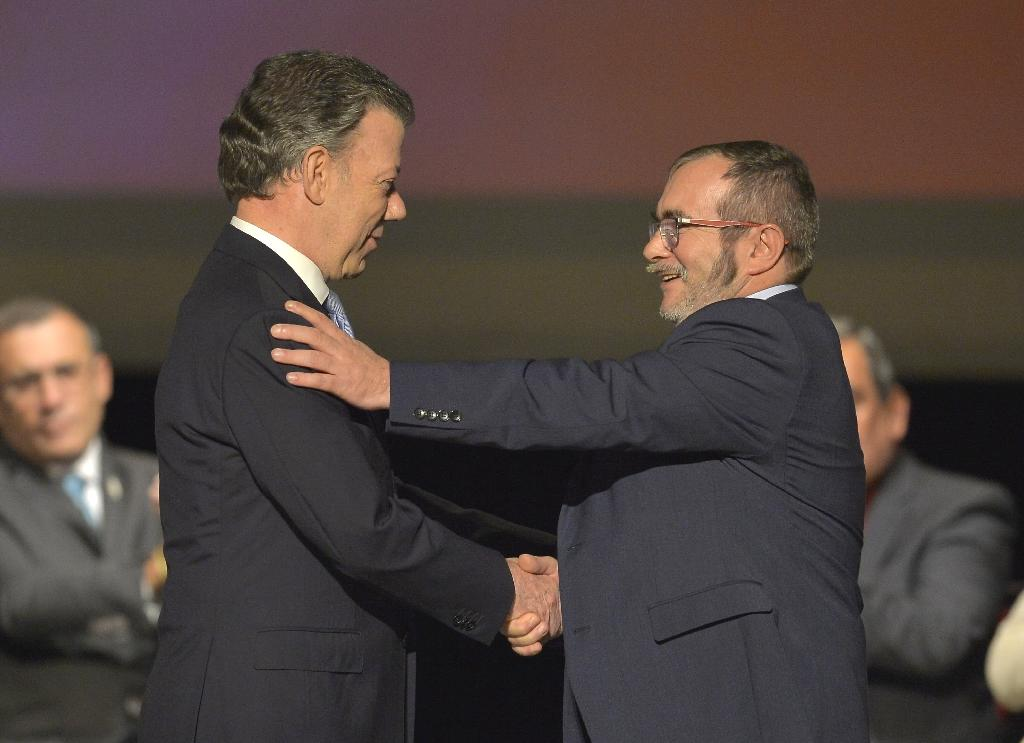 President Juan Manuel Santos (L) and head of the FARC guerrilla Timoleon Jimenez, aka Timochenko, shake hands during the second signing of the peace agreement at Colon Theater in Bogota, Colombia, on November 24, 2016 (AFP Photo/Luis Robayo)