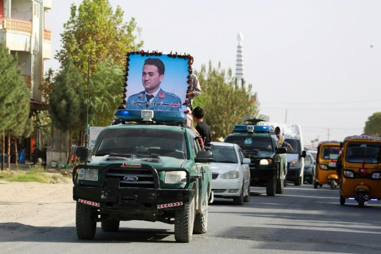 Mourners display a portrait of Kunduz police spokesman Sayed Sarwar Hussaini, killed by a suicide bomber while he spoke to reporters (AFP Photo/STR)