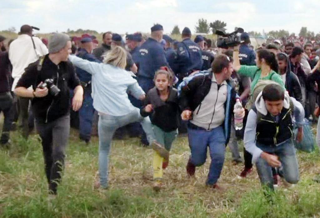 Hungarian TV camerawoman Petra Laszlo (with back to camera) was acquitted by the country's Supreme Court of vandalism after she kicked a child running with other migrants from a police line in Roszke, southern Hungary on September 9, 2015