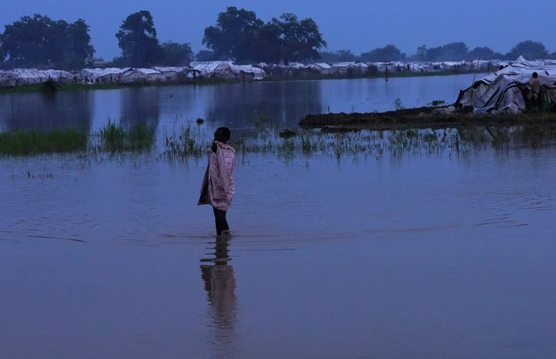 A displaced child wades through floodwaters after the River Nile broke the dykes in Pibor