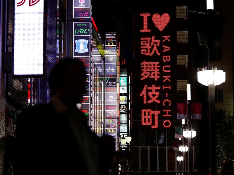 FILE PHOTO: A passerby is seen in Kabukicho nightlife district, during a state of emergency to fight the coronavirus disease outbreak, in Tokyo