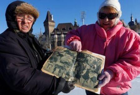 Two elderly women show a 1936 newspaper with a pictures story about the City Park Ice Rink in Budapest, Hungary, January 6, 2017. REUTERS/Laszlo Balogh