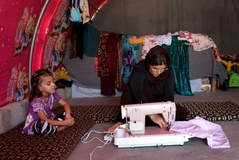 Yazidi survivor Layleh Shemmo sews inside her tent in the Khonke displacement camp in northwestern Iraq on June 24, 2019 (AFP Photo/SAFIN HAMED)