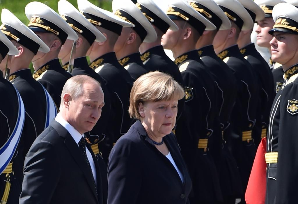 Russian President Vladimir Putin (L) and German Chancellor Angela Merkel attend a wreath-laying ceremony at the Tomb of the Unknown Soldier by the Kremlin Wall in Moscow on May 10, 2015 (AFP Photo/Kirill Kudryavtsev)