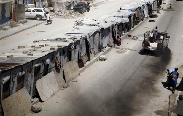 A truck leaves a trail of smoke in a street known as Route des Rails in Port-au-Prince, July 21, 2010.