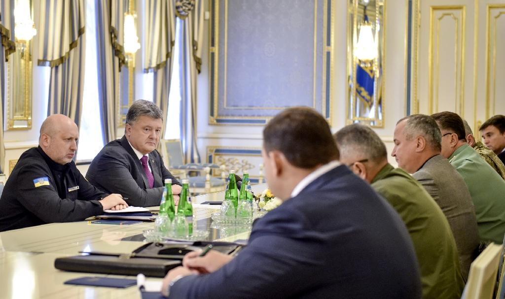 Ukrainian President Petro Poroshenko (2L) speaks to the country's high-ranking military officials during their meeting