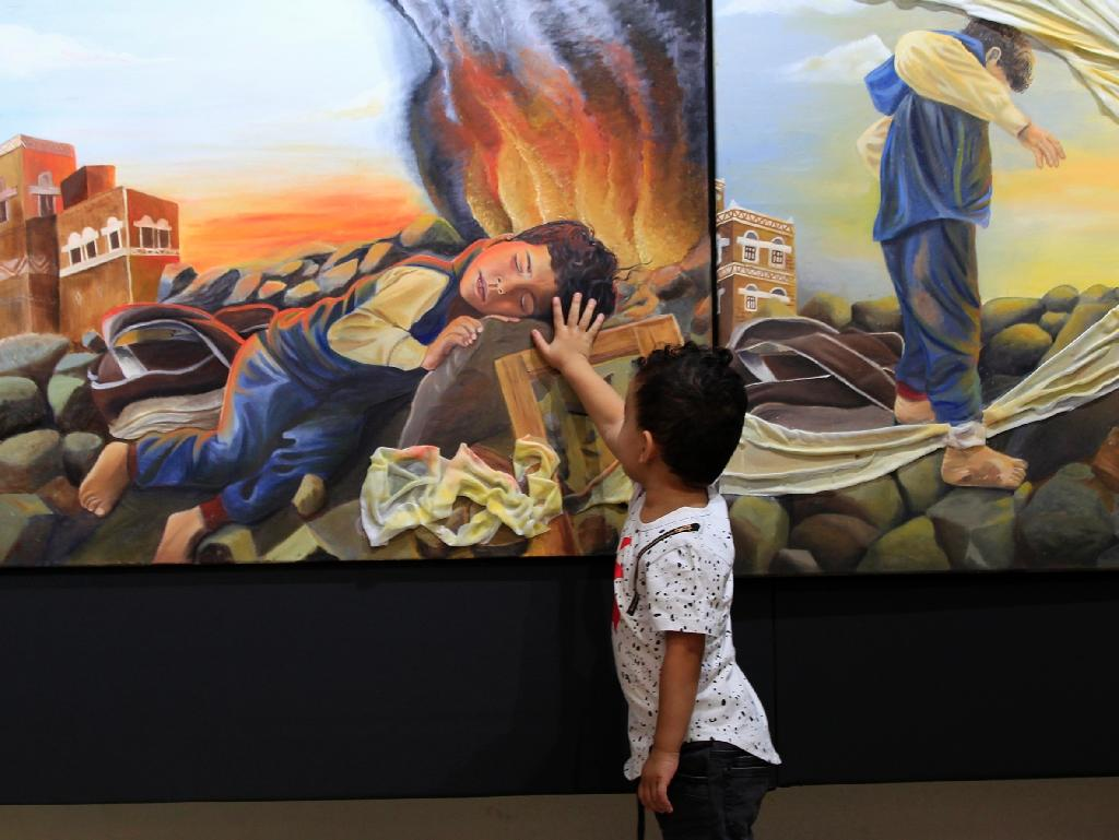 A Yemeni child touches a painting at an anti-war art exhibition in the capital Sanaa on October 1, 2018 (AFP Photo/MOHAMMED HUWAIS)