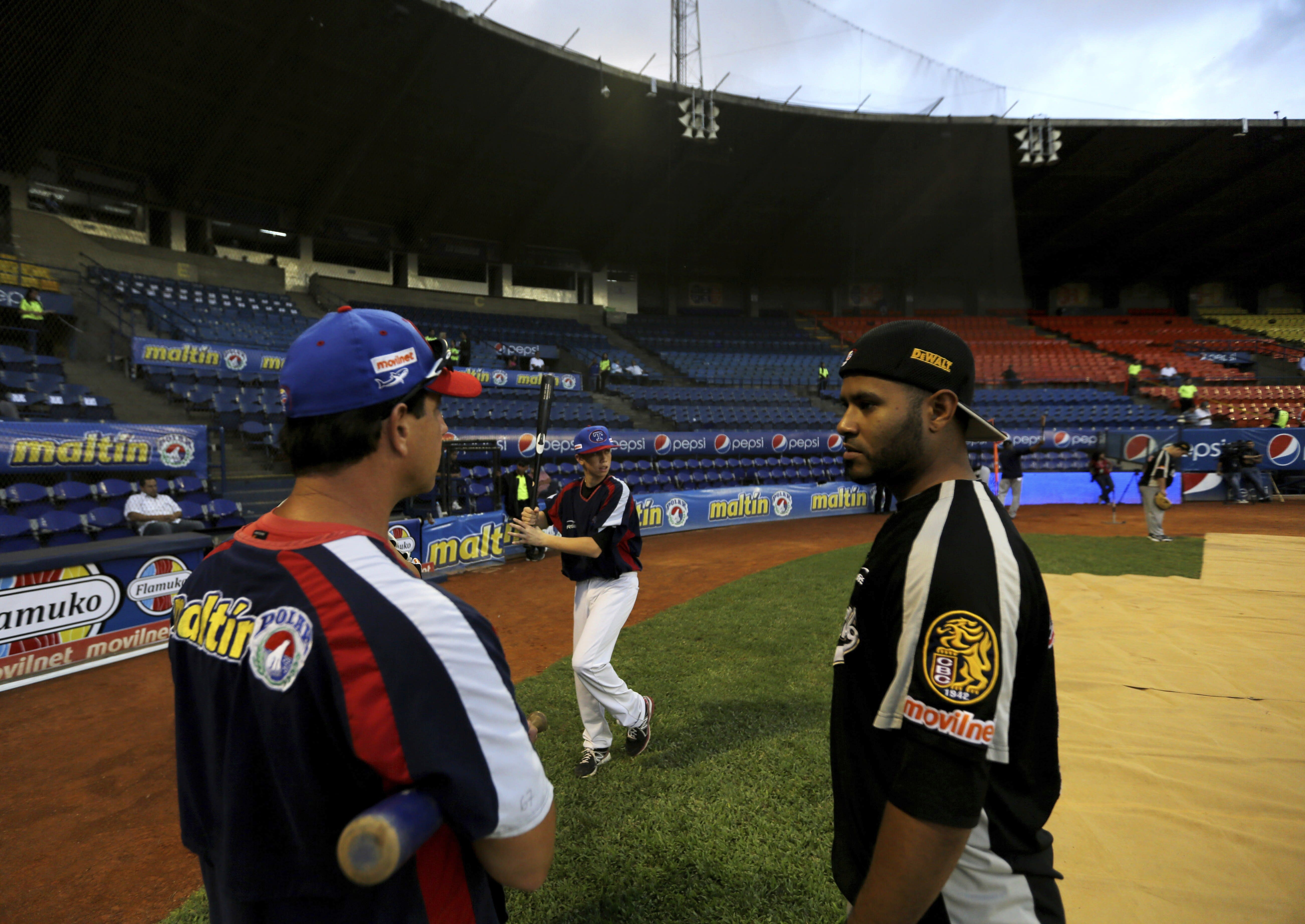 FILE - In this Nov. 27, 2013, photo, Anthony DeFrancesco, center, son of Tiburones head coach Tony DeFrancesco, left, practices his baseball swing as his father speaks with a player prior to a baseball game against rival Leones, at Estadio Universitario in Caracas, Venezuela. Major League Baseball is banning players from participating in the Venezuelan Winter League in one of the first public repercussions of new U.S. economic sanctions against the Venezuelan government. MLB said Thursday, Aug. 22, 2019, it is in contact with the U.S. government to determine how to proceed under the new sanctions against President Nicols Maduro's administration and at least temporarily suspending involvement in the league. (AP Photo/Fernando Llano, File)