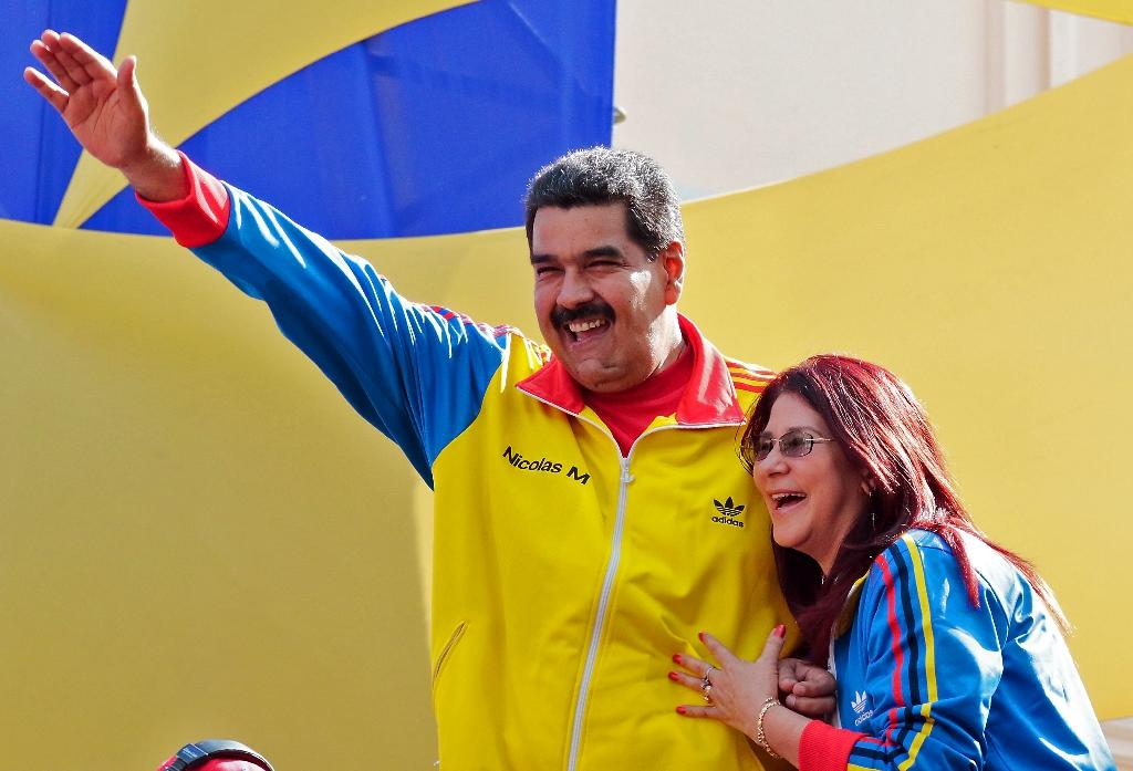 Handout photo released by the Venezuelan Presidency of President Nicolas Maduro (L) waving next to First Lady Cilia Flores (R) during a rally in Caracas on August 28, 2015 (AFP Photo/)