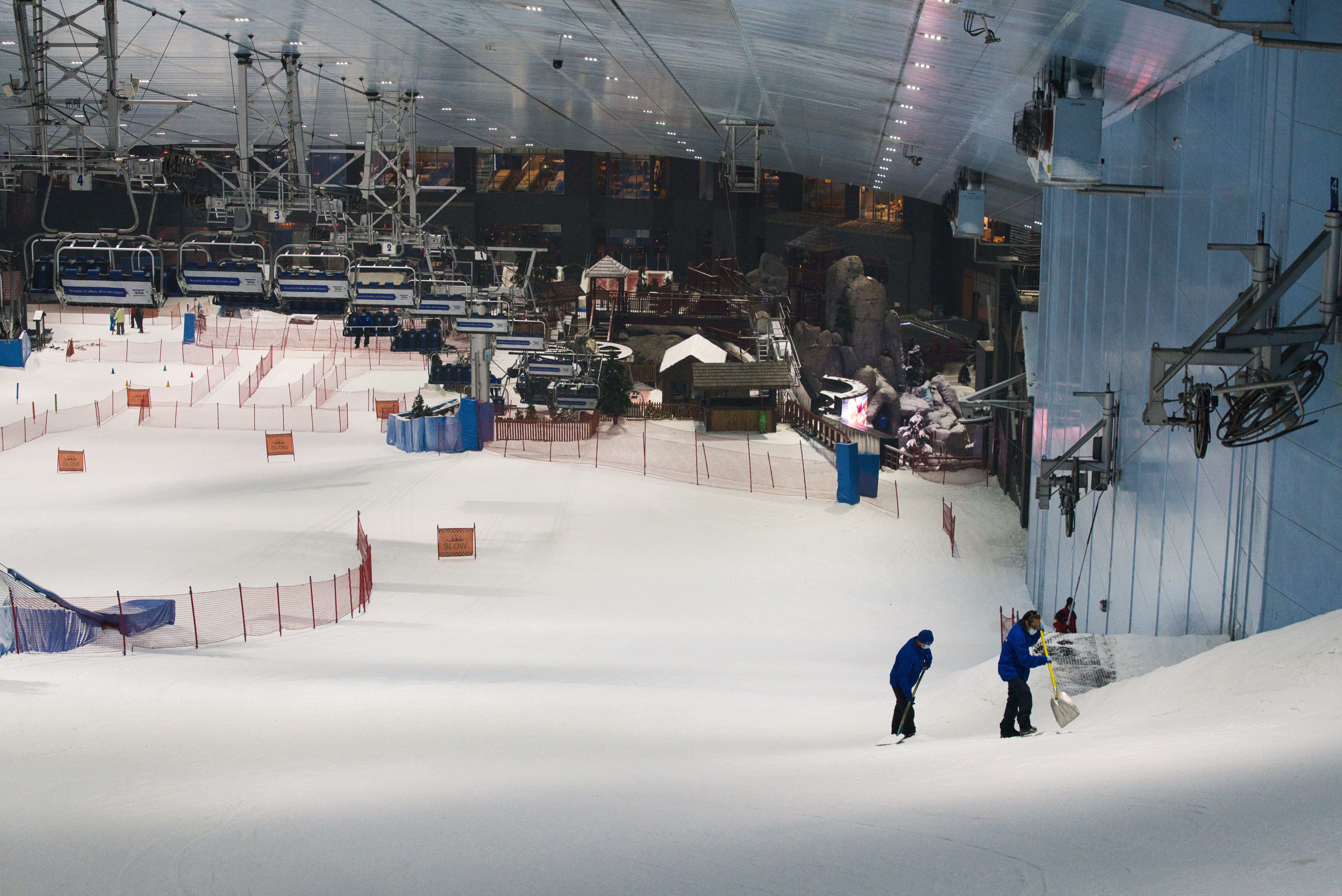 Two employees of Ski Dubai pack snow at Mall of the Emirates in Dubai, United Arab Emirates, Wednesday, May 27, 2020. Dubai on Wednesday loosed its restrictions imposed over the coronavirus pandemic, allowing movie theaters and other attractions to operate. (AP Photo/Jon Gambrell)