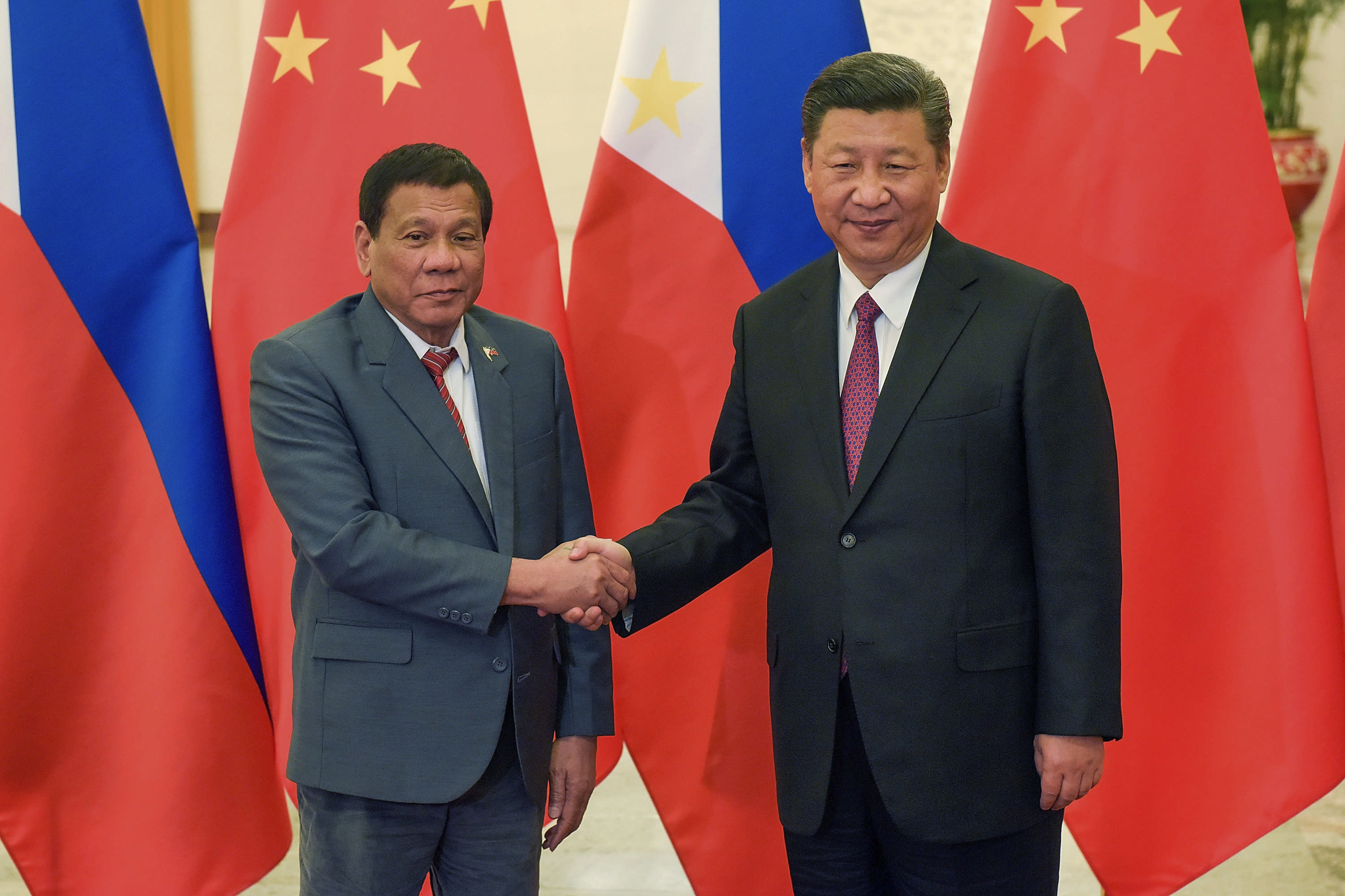 FILE - In this May 15, 2017, file photo, Philippine President Rodrigo Duterte, left, and Chinese President Xi Jinping pose for photographers prior to their bilateral meeting held on the sidelines of the Belt and Road Forum for International Cooperation at the Great Hall of the People in Beijing. Duterte is preparing to make his fifth visit to China later this month during which he says he will finally raise the result of the 2016 Hague arbitration on China's South China Sea claims amid a new spike in tensions. (Etienne Oliveau/Pool Photo via AP, File)