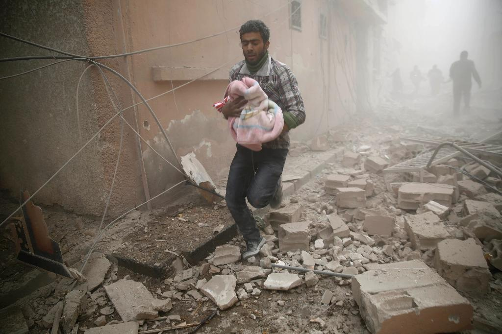 A Syrian man carries a baby wrapped in a blanket following air strikes on the town of Douma in the eastern Ghouta region, a rebel stronghold east of the capital Damascus, on December 13, 2015 (AFP Photo/Sameer Al-Doumy)