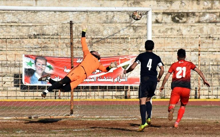 Al-Ittihad's goalkeeper dives to make a save during a Syrian league football match between derby rivals Al-Ittihad (in red) and Al-Hurriya, in the northern city of Aleppo in January 2017