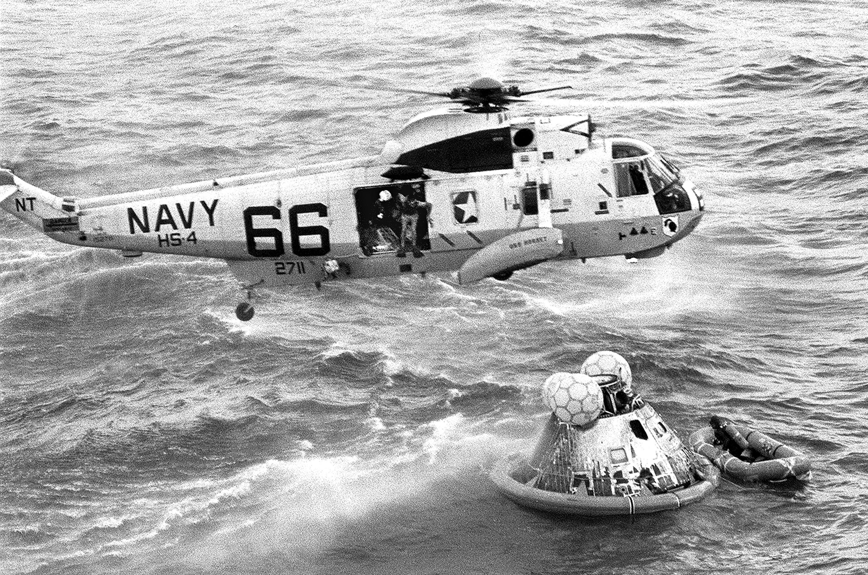 In this July 24, 1969 photo from the U.S. Navy, Navy UDT swimmer Clancy Hatleberg prepares to jump from a helicopter into the water next to the Apollo 11 capsule after it splashed down in the Pacific Ocean, to assist the astronauts into the raft at right. Hatleberg was the first to welcome Apollo 11's moonmen back to Earth. (Milt Putnam/U.S. Navy via AP)