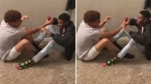 Two guys rub feet on rug to create static electricity and light a bulb