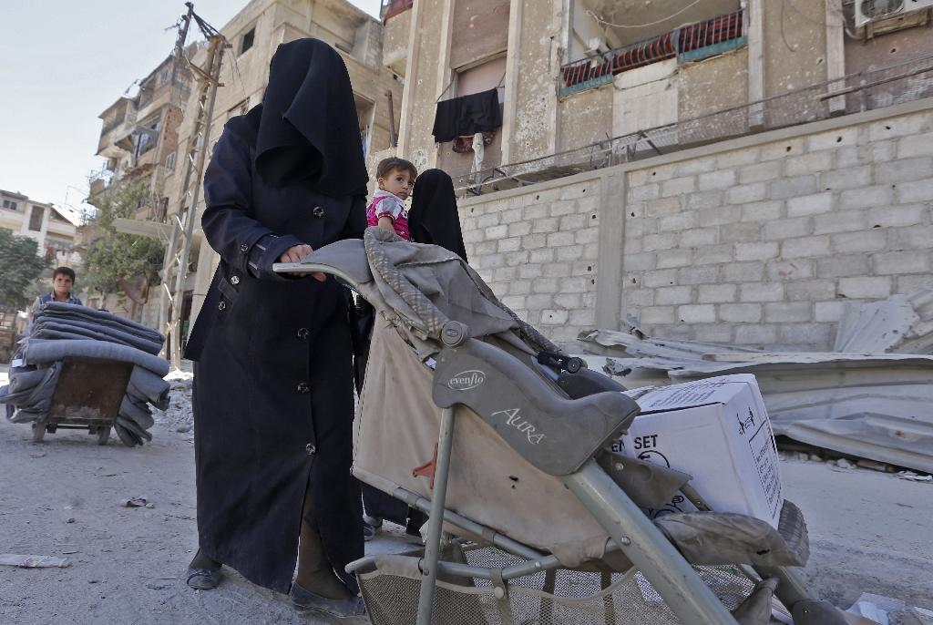 A woman in Douma uses a pram to carry humanitarian aid distributed by relief workers and the United Nations (AFP Photo/LOUAI BESHARA)